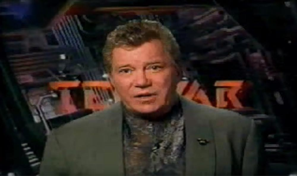 William Shatner in a green suit in front of the TekWar logo